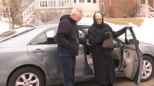 Volunteer driver, Larry Miller, assists DuRide member, Sue Lindsay, out of his car at the end of their ride.