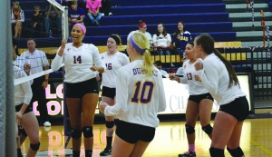 Junior Taylor Serrano celebrates with her fellow Duhawks after scoring a point against Luther.